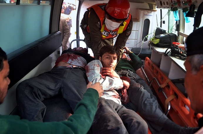 According to preliminary information, six militants riding motorcycles drove up to the school and started shootng at the security guards. Photo: Pakistani rescue workers take out students from an ambulance who were injured in the shootout at a school under attack by Taliban gunmen