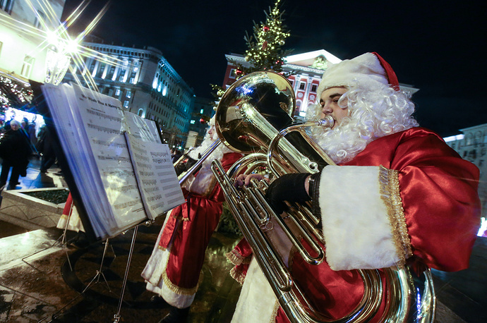A musician dressed as Father Frost (Russian Santa Claus) playing a trumpet at Tverskaya Square, Moscow