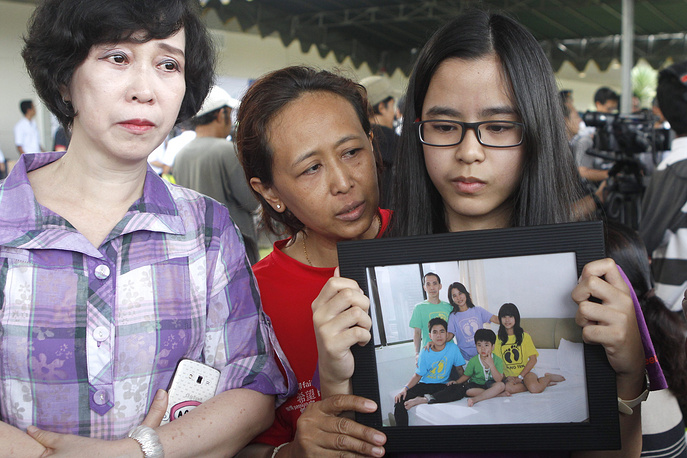 The Airbus A320-200 was carrying 155 passengers, including seven crewmembers. Photo: Relatives hold a picture of family members as they wait for news from the missing AirAsia plane at Juanda Airport, in Surabaya, Indonesia, 29 December 2014