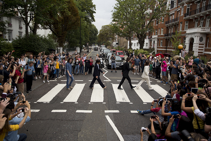 """The cast of the West End Beatles musical show """"Let it Be"""" attempting to recreate the cover photograph of the Beatles album """"Abbey Road"""" on the zebra crossing on Abbey Road in London"""