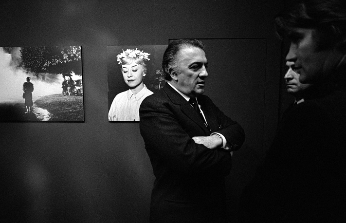"""Federico Fellini in front of a portrait of his wife, Italian actress Giulietta Masina, 1970 at the opening of an exhibition of still photographs from his film """"Le Notti di Cabiria"""" (Nights of Cabiria) in Germany.  Fellini won his second Academy Award for this film in 1957"""