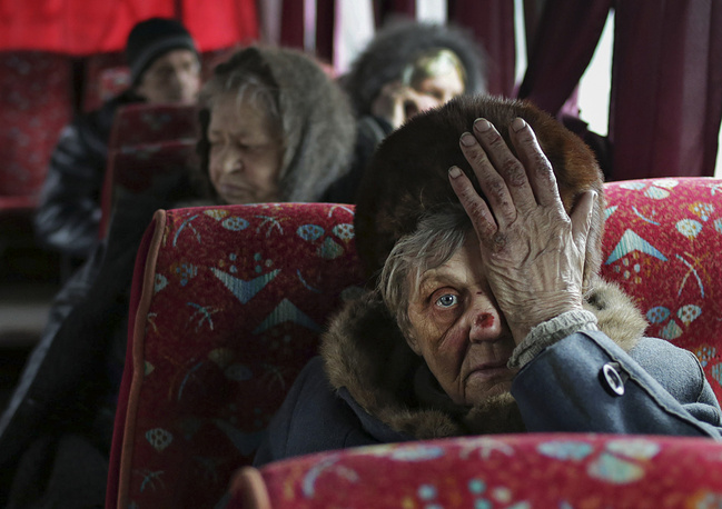 As shelling in Donetsk region continues, people try to escape from the zone of combat operations. Photo: Local citizens sit in a bus as they wait to evacuation from Debaltseve of Donetsk area, Ukraine