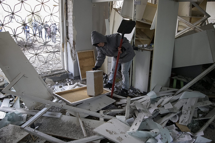 27th hospital in Tekstilshchik residential district in east Ukrainian city of Donetsk was heavily shelled on Febrary 4th leaving several people dead and wounded. Photo: A woman clears up debris at a damaged hospital after shelling in Donetsk