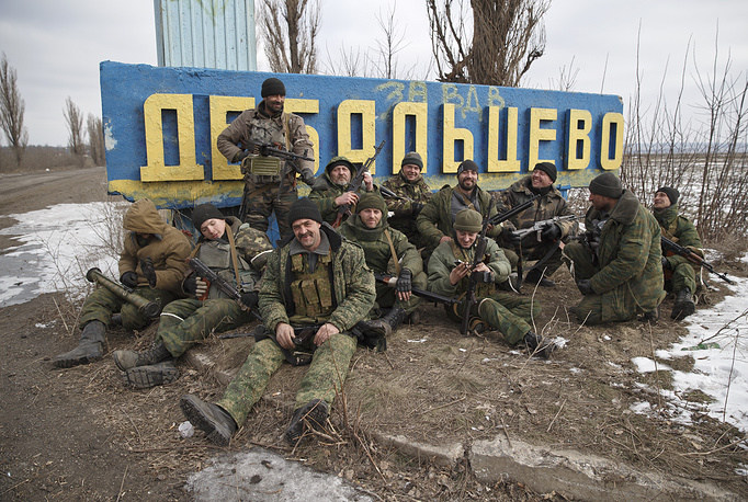 Photo: Militia fighters posing by a road sign at the entrance in Debaltsevo, Ukraine, after checking the access road into town for mines left behind by retreating Ukrainian government troops