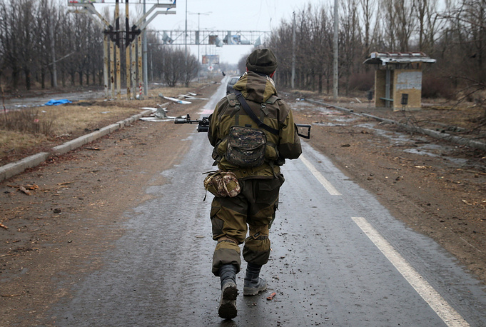 Militia man of the Donetsk region walking along the road near the destroyed Donetsk airport