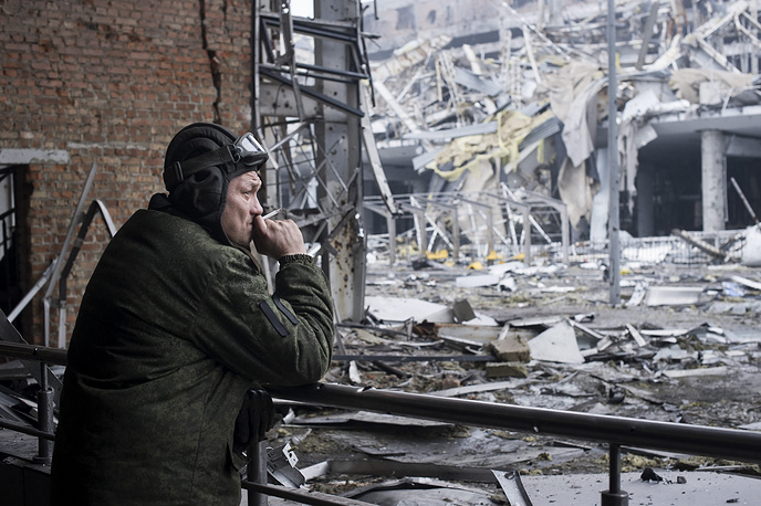 Militia man looking at the destroyed Donetsk airport