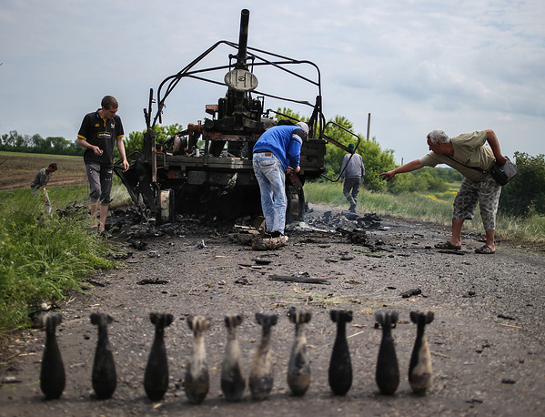 Local residents near a burnt out military vehicle in the aftermath of a military clash between Donetsk region militia and the Ukrainian government's forces near the village of Oktyabrskoye, Donetsk region, May 2014
