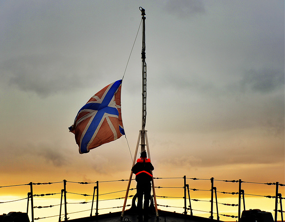 A jack flag being hoisted over the Russian cruiser Varyag during the joint Russian-Chinese military exercises