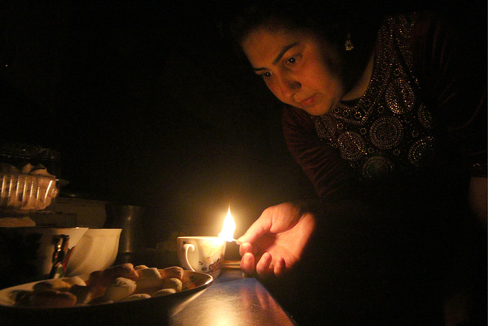 A woman lighting a candle at home in Crimea