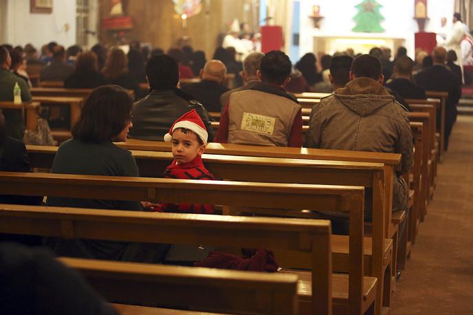 Iraqi Christians at a Christmas Eve Mass at St. Teresa church in Basra, 550 kilometers southeast of Baghdad, Iraq