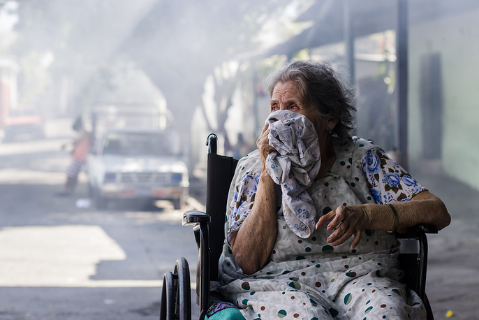 An old woman seen while city workers fumigate her home to combat the Aedes Aegypti mosquitoes at the San Judas Community in San Salvador, El Salvador