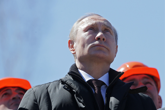 Russia's President Vladimir Putin watching a Soyuz-2.1a rocket booster carrying  satellites blast off from a launch pad at the Vostochny Cosmodrome