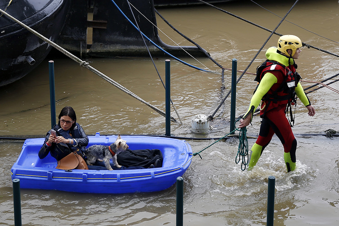 A fireman pulls a woman and her dog to shore, by a row of houseboats on the river Seine in Paris, France