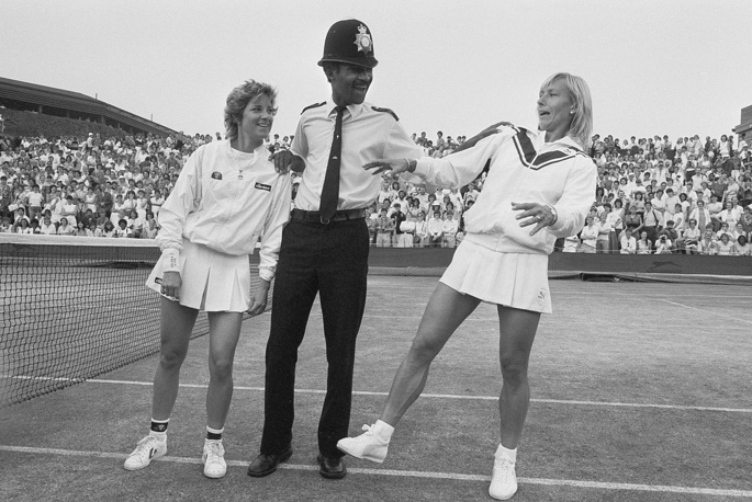Czech and US player Martina Navratilova is the winner of most Ladies' Singles titles (9) including six of them consecutively (1982-1987). Photo: Chris Evert and Martina Navratilova posing with Police Constable at Wimbledon, England, 1985