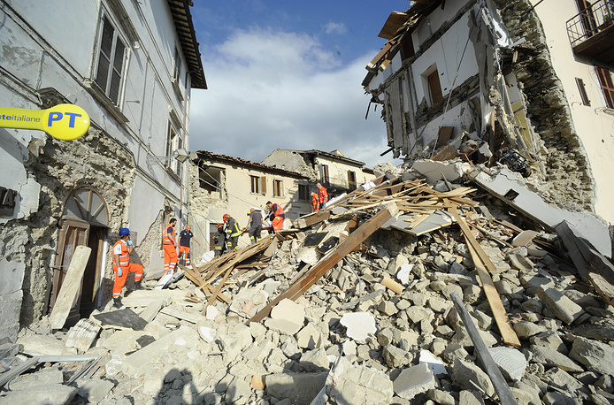 A man is carried on a stretcher after being rescued in Arquata del Tronto