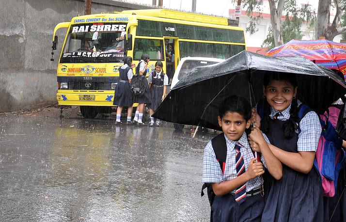 School children shelter under umbrellas in Bhopal, India