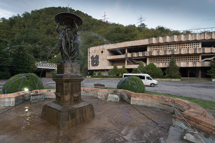 A fountain with an abandoned shopping center in Gagra