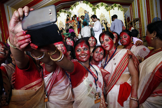 Hindu women take a selfie in front of an idol of goddess Durga on the last day of Durga Puja festival in Mumbai, India, October 11