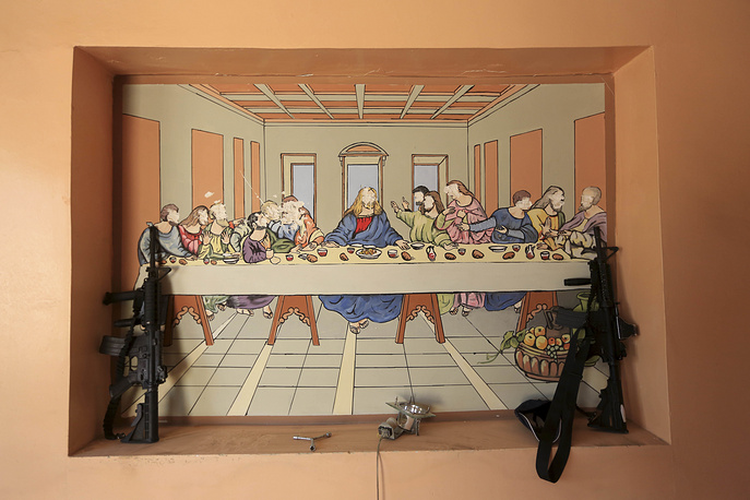 Weapons belonging to resting members of Iraq's elite counterterrorism forces placed near a depiction of the Last Supper, damaged by Islamic State fighters, at a house in Bartella