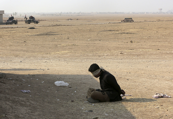 A handcuffed suspected Islamic State militant sits outside his house in the village of Tob Zawa, outside Mosul