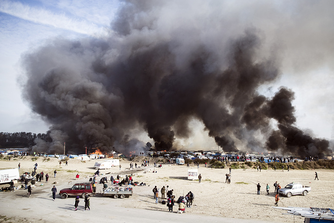 """Smoke billows from a fire after tents and shacks were set ablaze in the makeshift migrant camp known as """"the jungle"""" near Calais, France, October 26"""