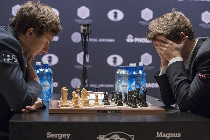 Sergey Karjakin, of Russia, and Magnus Carlsen, of Norway, concentrate on the board during the tie breaker round of the World Chess Championship in New York, November 30