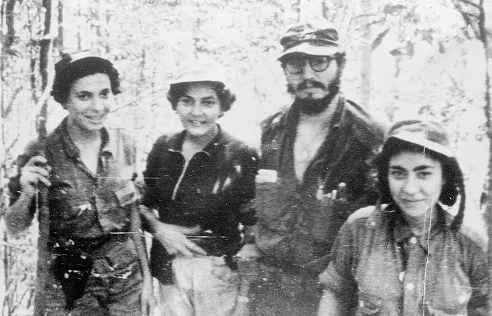 """In November 1958, Fidel Castro personally led his forces into battle near Guisa, not far from the island's second most important city of Santiago de Cuba. It was the start of the rebel army's final offensive. Photo: Cuban rebel leader Fidel Castro and nurses who worked for the rebel army """"Movement 26th July"""" in the Sierra Maestra, Cuba, 1958"""
