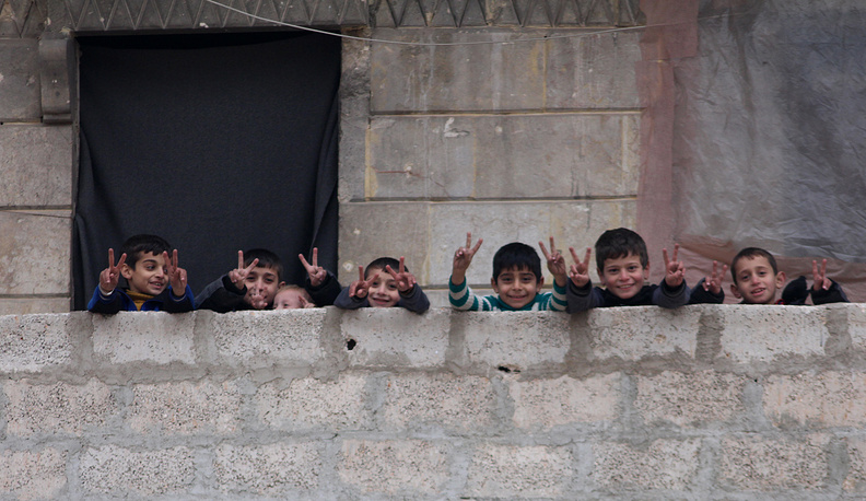 Children flash the victory sign from one of the houses in Salah al-Din neighborhood, east of Aleppo