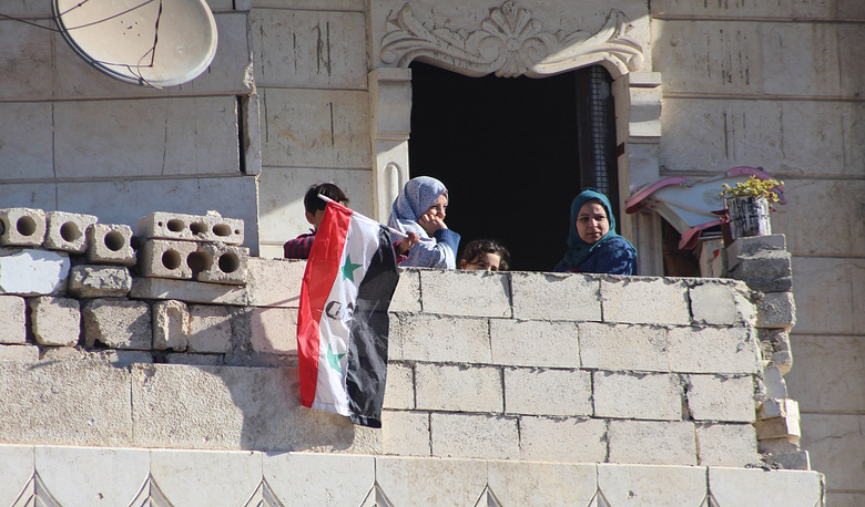 Syrian citizens watch the evacuation of fighters and their families from rebel-held zones in Aleppo