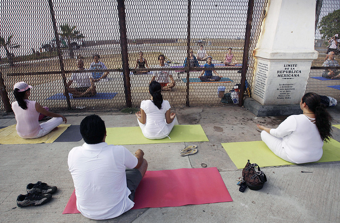"People practicing yoga on both sides of the US-Mexico border fence as they take part in the ""Yoga without borders"" encounter in Tijuana, Mexico, 2008"