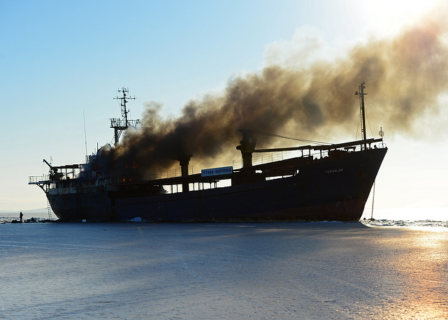 Smoke rises over the ghost ship Yeruslan, at anchor in the Amur Bay waters, Russia, January 31