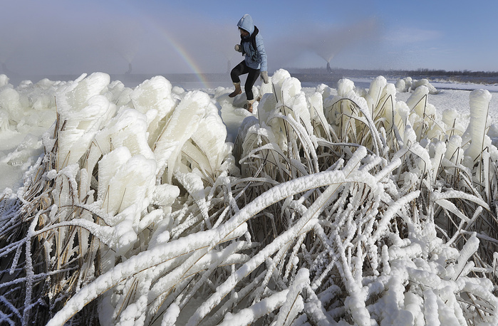 A woman walks through ice-covered grass with a rainbow visible in the back, near the town of Rudensk, Belarus, February 7
