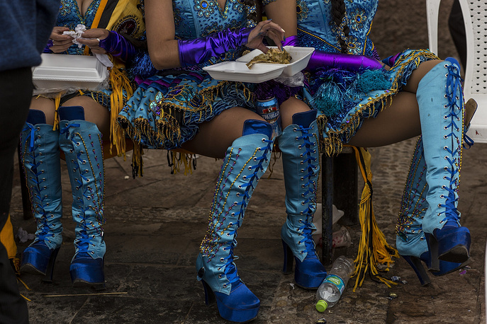 Dancers eat lunch during a break from performing at the Virgin of Candelaria celebrations in Puno, Peru, February 5