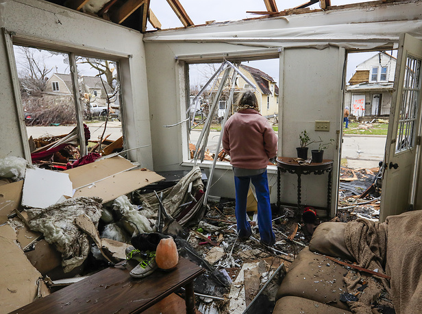 A woman looks out the window of her living room as she begins to clean up after a tornado destroyed her home in Naplate, Illinois, USA, March 1