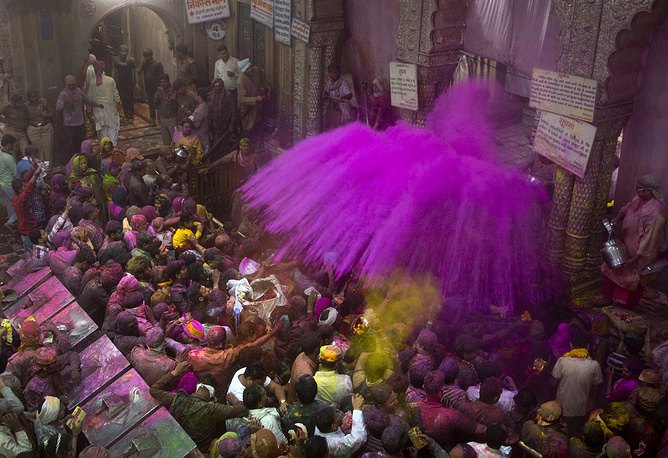 Hindu priests throw color powders at the devotees inside Banke Bihari temple, dedicated to Lord Krishna, during Holi festival celebrations in Vrindavan, India, March 8