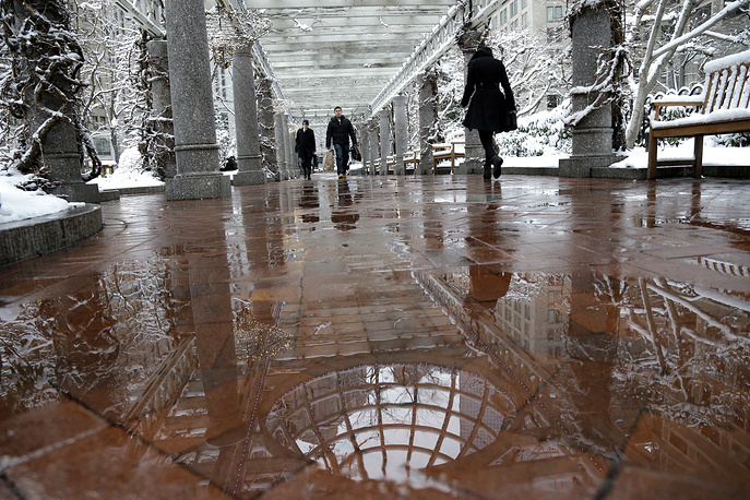 Pedestrians walk under a large trellis as snow falls in Boston