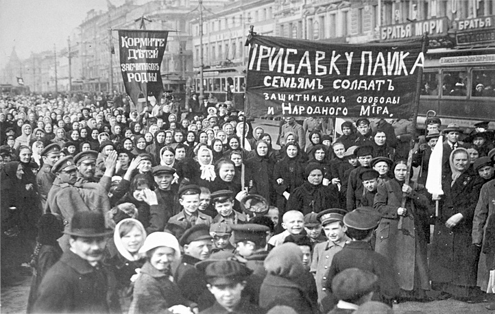 """A demonstration of workers from the Putilov plant in Petrograd. The left banner reads """"Feed the children of the defenders of the motherland""""; the right banner, """"Increase payments to the soldiers' families - defenders of freedom and world peace"""",  March 1917"""