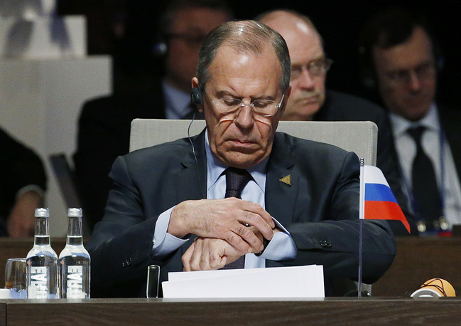 Russia's Foreign Minister Sergey Lavrov checks his watch during the opening session of the Nuclear Summit in The Hague, the Netherlands, 2014