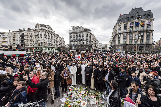 People stand for a moment of silence at the Bourse to honor the victims of the Brussels terror attacks marking one year after the tragedy, March 22