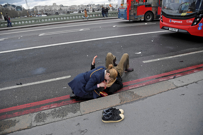 A woman assists a terror attack victim at the Westminster Bridge in London, UK, March 22