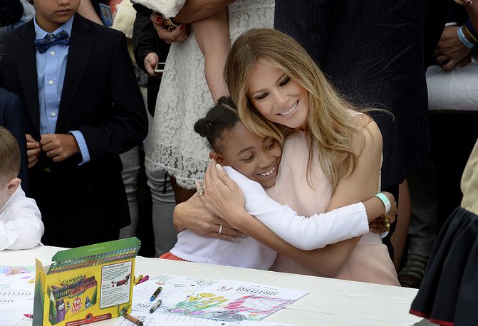 US First Lady Melania Trump hugs a girl as they make cards for members of the military at the annual Easter Egg roll in White House, Washington, USA, April 17