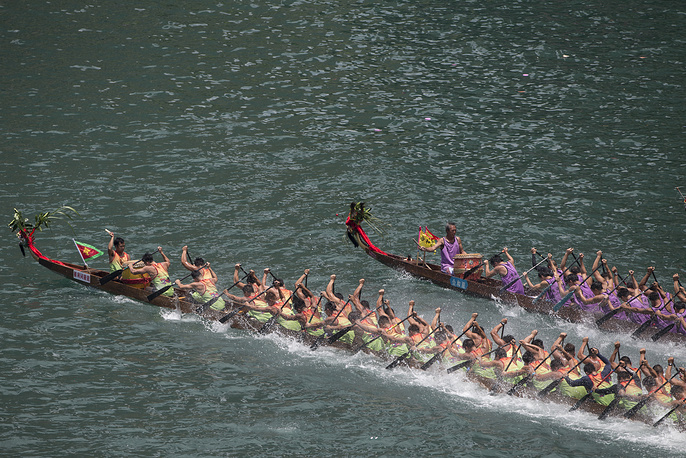 Dragon boat teams race in Aberdeen fishing harbour in Hong Kong