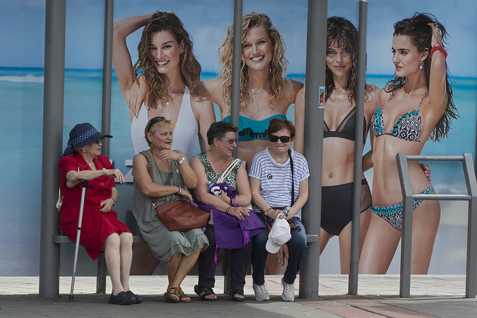 Four women wait at a bus stop in front of an advertising poster for swimwear and beach wear in Madrid, Spain, May 27