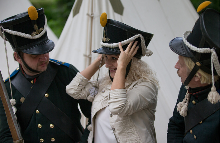 A woman tries on a headpiece during the Times and Epochs historical reenactment festival.