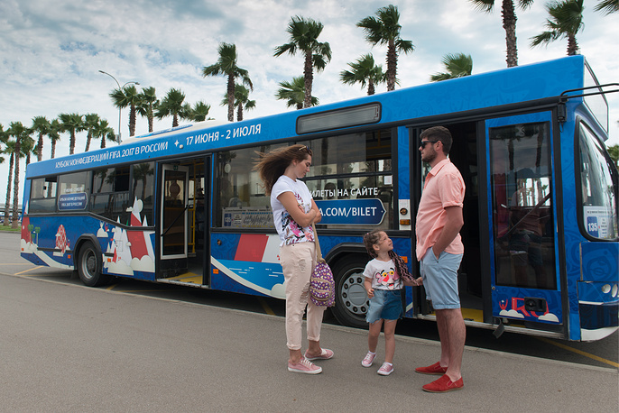 A family by a 2017 FIFA Confederations Cup branded bus at a public transport stop in Sochi, one of the host cities for the tournament