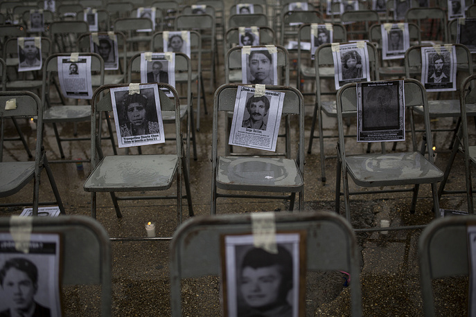 "Chairs bearing portraits of people who were disappeared during the 1980's, sit empty in a ceremony marking the National Day of the Disappeared in Guatemala City, June 21. According to human rights groups, more than 40,000 people were ""disappeared"" during Guatemala's 36 years of internal conflict"