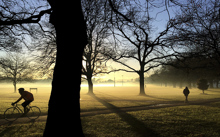 Commuters make their way through a mist covered Hagley Park in central Christchurch, New Zealand, June 26