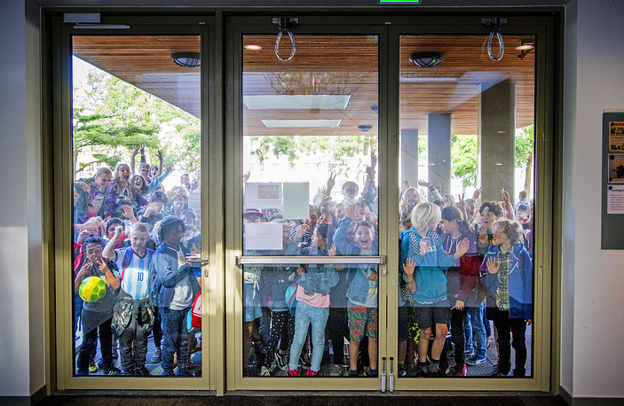 Children wait at the entrance doors as primary school teachers go on strike, during a protest against the teacher's shortage, work pressure and poor salaries, in Rotterdam, The Netherlands, June 27