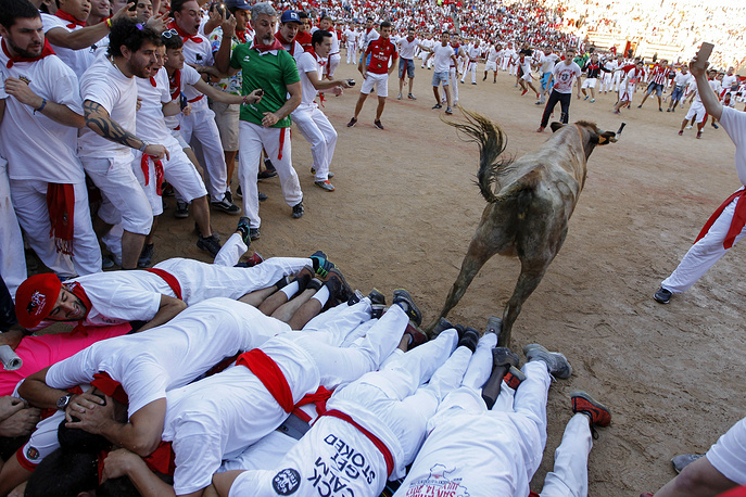 A cow jumps over a group of revellers laid on the ground of the bullring, during the running of the bulls at the San Fermin Festival, in Pamplona, Spain, July 12