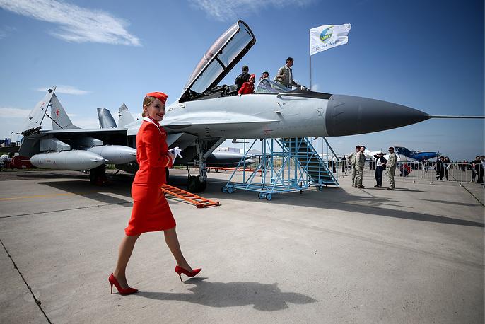 An Aeroflot flight attendant walks by a Mikoyan MiG 29K fighter jet